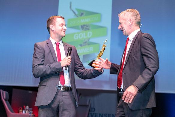 """Nils Othersen überreicht Gerhard Kreutz, dem Geschäftsführer der Bad Bevensen Marketing GmbH, bei der Veranstaltung """"1 Jahr in 100 Minuten"""" im Kurhaus Bad Bevensen den internationalen Marcom Award 2018, mit dem die Kampagne ausgezeichnet wurde."""