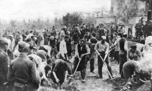 Von der SS zusammengetriebene jüdische Männer, Frauen und Kinder schaufeln ihr eigenes Grab.