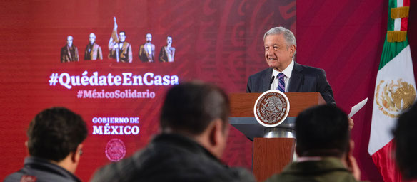 "President López Obrador at a press conference during the health crisis, with the slogan ¡Quedate en casa! ""Stay at home"" in the background (header photo of his official Facebook page)."