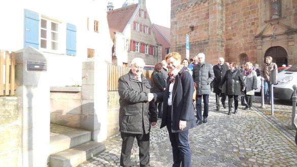 Melanie Bößl und Josef Zimmermann reichen sich nach dem Gottesdienst auf dem Platz vor der St. Emmeramskirche in Spalt die Hand