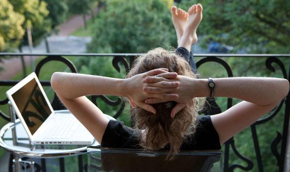 mädchen sitzt am balkon und lehnt sich entspannt zurück