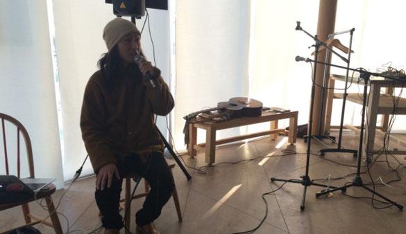 金丸 文武が椅子に座り、世界一周の旅の体験談を説明している場面