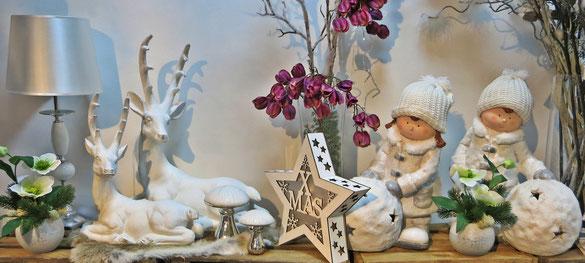 Deko Figuren, Teelichthalter und Seidenblumen Gestecke in weihnachtlichen Farben.