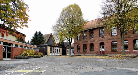 Rechts im Bild der Hauptgebäudeteil von 1896, im Hintergrund in der Mitte zwei Schulpavillons von 1967 und links die 1977 fertig gestellte Turnhalle. Aufnahme von 2016