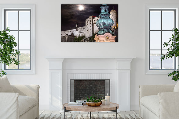 A picture of the Fortress Hohensalzburg at full moon hangs above a fireplace. (c) www.strobgalerie.at