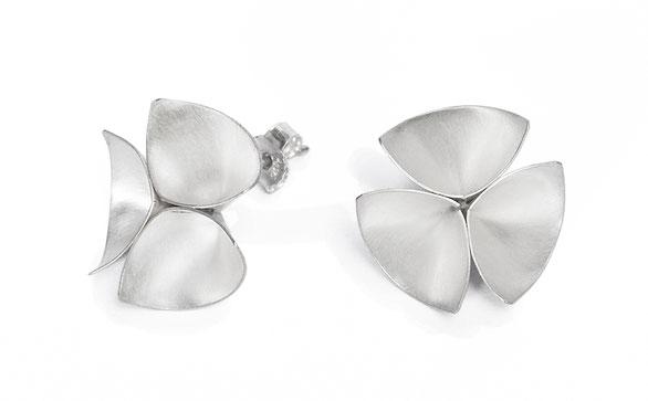 Die wunderbar grazilen Ohrstecker TALLINA sind aus feinstem, weißlich schimmerndem Silber gearbeitet. Die zarte dreidimensional ausgearbeitete Form erinnert an eine Blüte oder ein Kleeblatt.