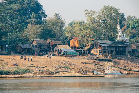 Auf dem Foto ist ein Dorf in Myanmar zu sehen. Es sind nur wenige Hütten am Flußufer. Dahinter befindet sich ein Wald.