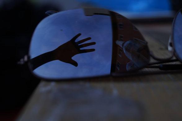 Stammtisch-Titelbild. Schatten einer Hand auf einer Sonnenbrille, in der sich der Abendhimmel spiegelt