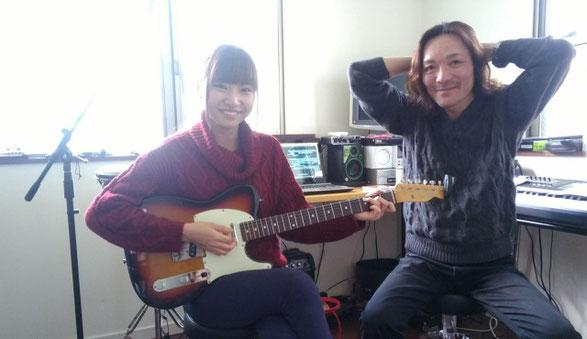ギターを持つ笑顔の女性と佐倉一樹先生