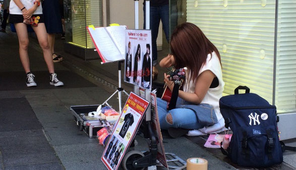 「眠らない兎」ボーカルの「あやめ」が千葉駅前で路上ライブをしている場面