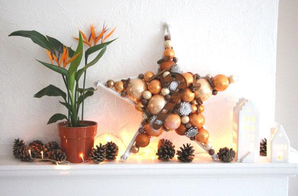 Handgefertigter Stern in warmen Erdfarben mit einer Zuckerstange aus Edelrost Metall mit Zapfen und Strelitzie auf Kaminsims dekoriert.
