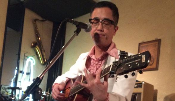 チャーリー坂本が横浜市にあるSam's Barで弾き語り演奏している場面