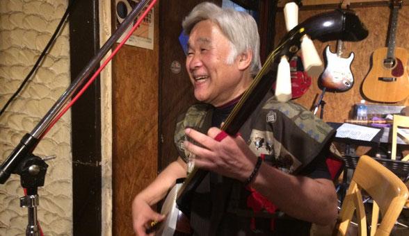 群馬県にある「Cafe Score」のステージで松本 梅頌先生が楽しそうに三味線を演奏している場面