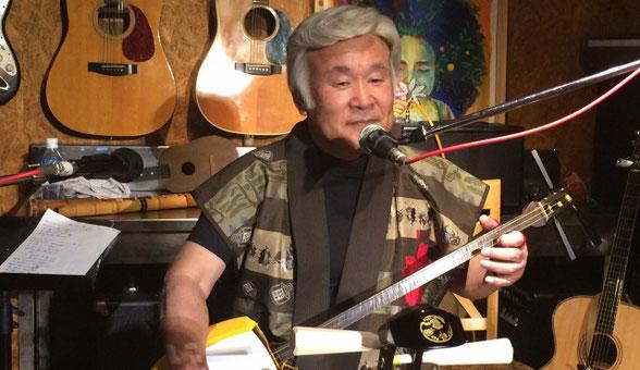 群馬県にある「Cafe Score」のステージで松本 梅頌先生が小林 進さんを褒めている場面