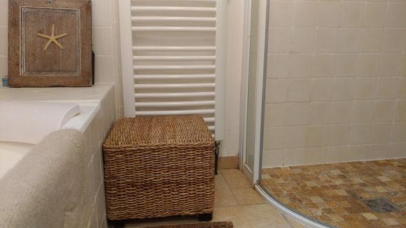 Salle de bain nature avec baignoire et faïences artisanales beiges, plan vasque en pierre blonde, meuble maçonné avec tiroirs en rotin tressé, tapis artisanal en laine mérinos, sèche-serviette en fer forgé.