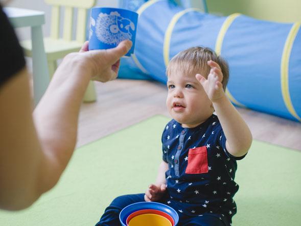 Ein kleines Kind greift nach einem blauen Becher. Foto: Martin Rink/Lebenshilfe Soltau e.V.