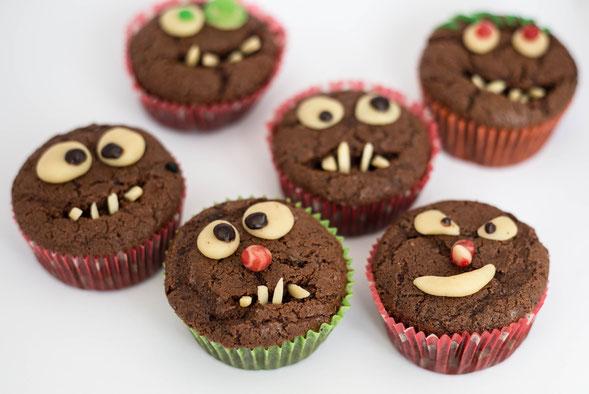 Schokomuffins dekoriert als kleine Monster mit Mandelzähnen und Marzipanaugen