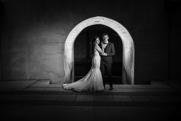 Black and white photo of a bride and groom in front of a lit archway. Bride is in a white dress and groom is in a suit.