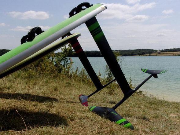 deux windfoils aeromod version 2, un noir et rouge cerise, un noir et vert pomme, à la Ganguise au bord de l'eau avec leur flotteur de planche à voile