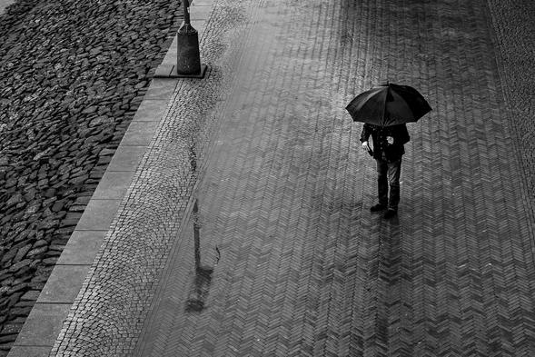 Ein Mann mit Regenschirm an der Bremer Schlachte, Fotograf Jürgen Deinert