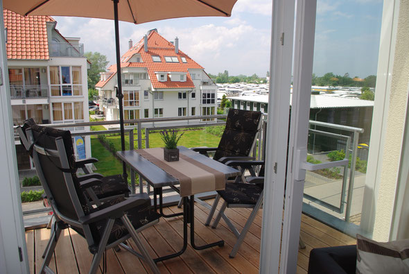 Balkon in Süd-West-Ausrichtung mit Tisch, 4 verstellbaren Hochlehnern, Sonnenschirm und Elektrogrill