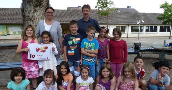 """Kinder der Ahrweiler Grundschule präsentieren gemeinsam mit Schulleiter Klaus Mührel (hinten rechts) und der Vereinsvorsitzenden Jessica Ulrich (hinten links) das Jubiläumslogo """"ihres"""" Fördervereins. (Foto: Jessica Ulrich)"""