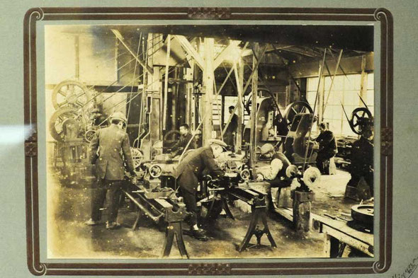 写真が貴重な時代に撮影された工場の写真。当時は、撮影に時間がかかったため機械も人も止まったまま撮影されました。服装もきちんとしていることから、記念撮影として撮影されたと思われます。