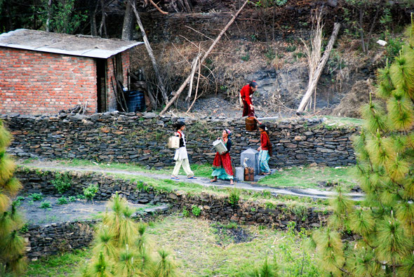 Women in the Kumaon Hills near Almora in Northern India replenish their drinking water supplies from the intermittent flow at this tap