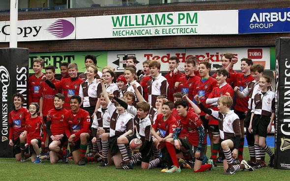 Gruppenbild mit Gastgebern im alt-ehrwürdigen Cardiff Arms Park Stadion auf hochmodernem Allwetter Rugby-Kunstrasen!