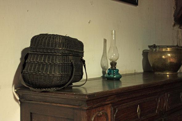 Een houten buffetkast met bovenop een petroleumlamp, een koperen ketel en een zwarte wissen eierenmand.