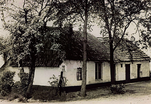 Zwart-wit foto. Een wit lemen boerderij met pannendak. Een kapelletje ervoor met enkele bomen.
