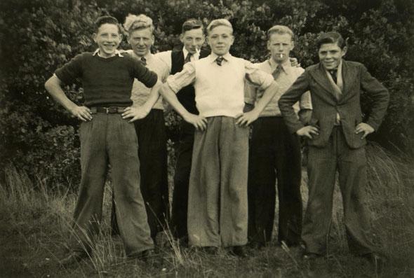 Zes jongens naast en achter elkaar. Zij staan voor een haag. Een zwart-wit foto. Foto genomen ongeveer 1946.