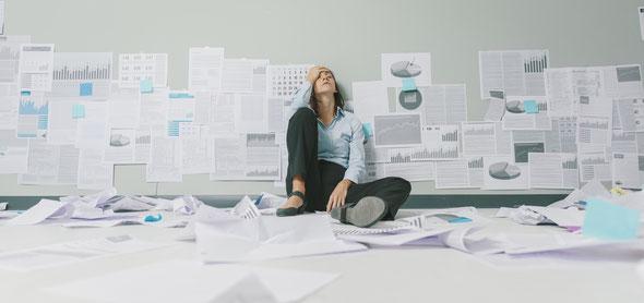 Mitarbeiter versinkt im Totalen Stress um ihn herum sind viele verschiedene Dokumente und er weiss nicht wo er anfangen soll