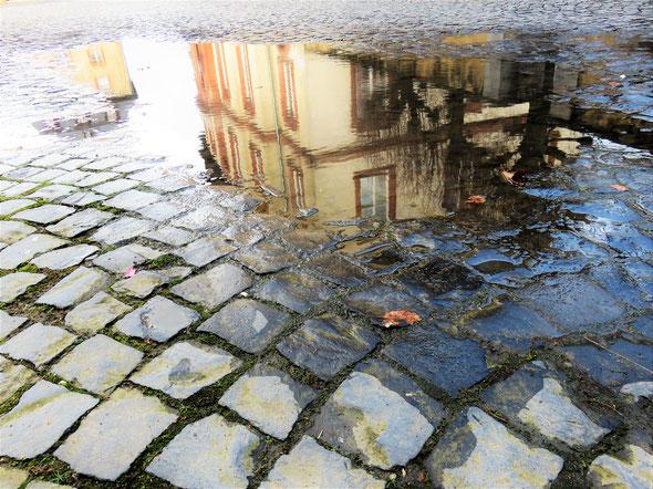 Historisches Rätselfoto № 1: Welches Gebäude spiegelt sich hier malerisch in den Pfützen des Kopfsteinpflasters? Viel Freude beim Mitraten! – Foto: ©Matthias Knaust