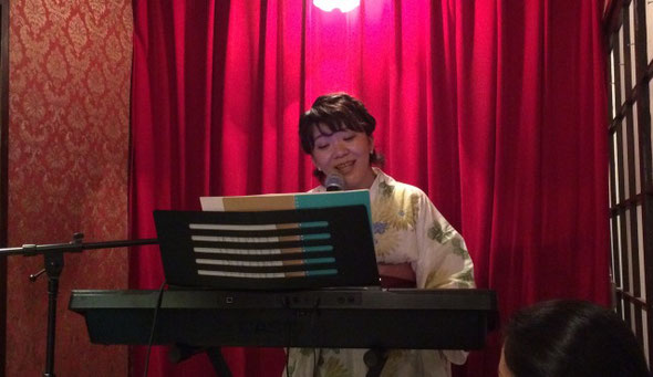 ミュージカル女優の「王子 菜摘子」がピアノの弾き語りをしている場面