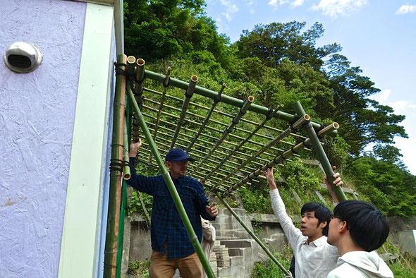 身近な素材を使って必要なものを作るブリコラージュという手法から、土地がもつ環境や知恵が見えてくる。作業を指揮する小山田徹(写真左)