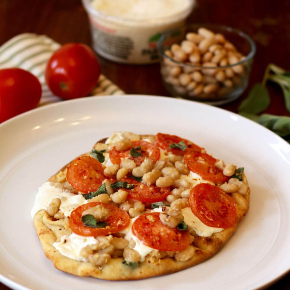 Eating healthy but missing pizza? Solution: white bean pizza. Naan bread pizza recipes are so easy—just finish with your favorite good pizza toppings, like veggies and cheese! #healthyeating #homemadepizza #flatbreadrecipes #vegetarian #highprotein