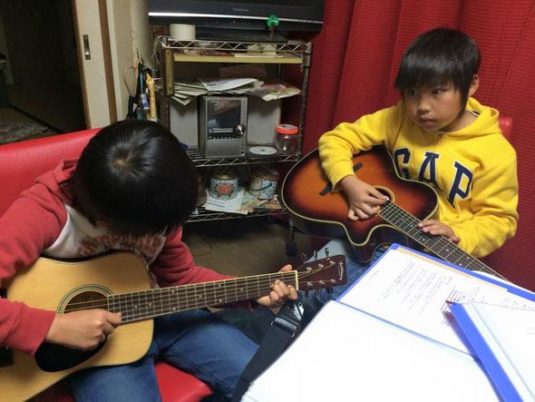 サッカー少年の小学生兄弟。弟は3/4スケールのミニギター。
