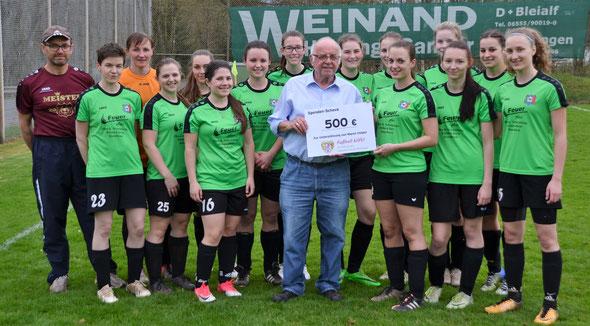 Walfried Hacken (Kreisvorsitzender Eifel) überreicht stellvertretend für die FVR-Stiftung einen Spendenscheck über 500 Euro an die Spielerinnen der SG Winterspelt