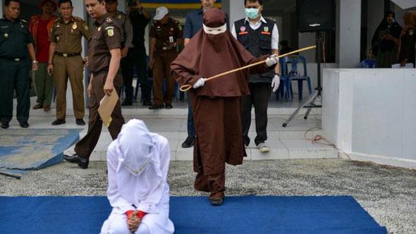Dans certaines régions du monde, la charia devient la loi imposant flagellation, amputations, lapidations. Une exécutrice sur le point de flageller en public une femme agenouillée, le 10 décembre 2019 à Aceh, en Indonésie, au XXIème siècle !