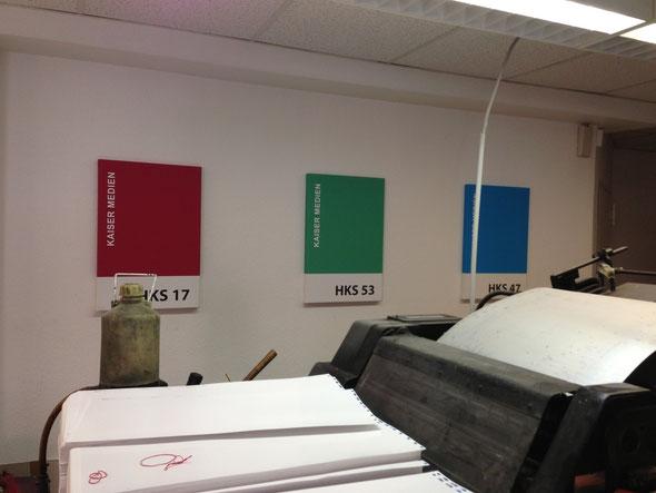 Sie sehen verschieden Farbige Keilrahmen die HKS Farben zeigen an einer Wand in der Druckerei