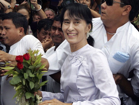 KHIN MAUNG WIN/AP Myanmar pro-democracy leader Aung San Suu Kyi, center, arrives at the headquarters of her National League for Democracy party Monday, April 2, 2012, in Yangon, Myanmar. Suu Kyi said she hopes her victory in a landmark election will mark