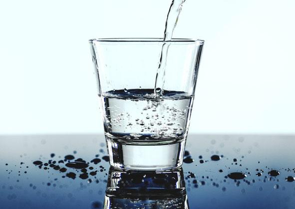 Ein Glas Wasser, das befüllt wird. Es steht auf einem blauen Tisch mit spiegelnder Oberfläche.