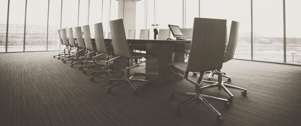 Großer Konferenzraum, mit großem Konferenztisch und leeren Stühlen.