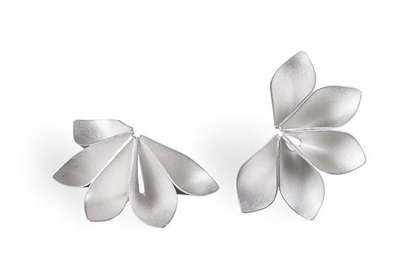 Die Ohrstecker MELA umrahmen mit ihrer blütenhaften Form Ihr Gesicht. Die zarte Silberblüte ist nicht ganz geschlossen, sie bildet einen Dreiviertelkreis