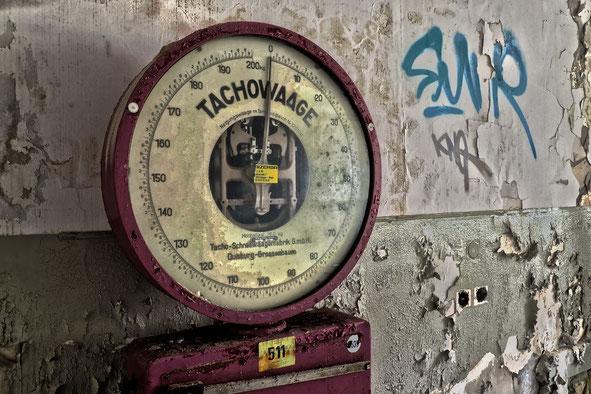 alte Tacho-Waage vor einer Sandsteinmauer mit Graffiti, Sylvia Jungo