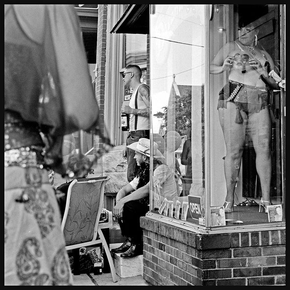 American Cowboy meets Striptease Window Performance. Analoge Hasselblad Black and White Picture shot on the streets of Baltimore by Berlin Artist Veruschka Bohn.