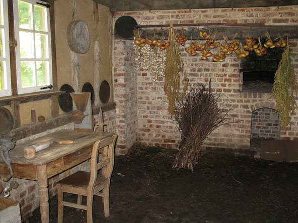 Binnenzicht oude hoeve. Met een tafel en één stoel. Een bussel hout en gedroogde ajuin boven de oven.