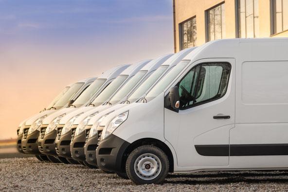 Weiße Vans in der Reihe aufgestellt