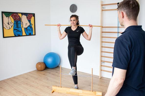 eine Frau steigt über eine Hürde bei einem Physiotherapeuten